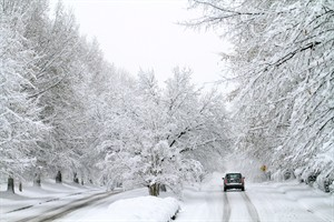 A car moves along a snow-covered road in the early morning in Raleigh, N.C., Sunday, Dec. 26, 2010. (AP Photo/Jim R. Bounds)