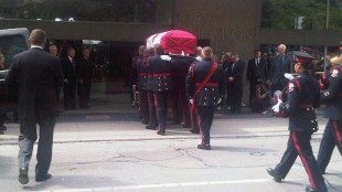 Members of an honour guard move the casket bearing Jack Layton into Roy Thomson Hall.