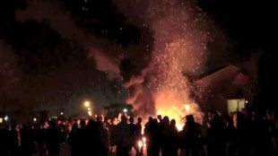 St. Patrick's Day revellers in London, Ontario watch a news van burn on March 17, 2012.