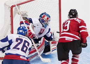 Canada forward Ryan Nugent-Hopkins, right, scores past Slovakia goalie Adam Nagy, centre, while Slovakia forward Branislav Rapac, left, looks on during third period IIHF World Junior Championships hockey action in Ufa, Russia on Friday, Dec. 28, 2012. THE CANADIAN PRESS/Nathan Denette