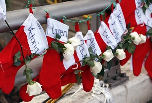 Christmas stockings with the names of shooting victims hang from railing near a makeshift memorial near the town Christmas tree in the Sandy Hook village of Newtown, Conn., Wednesday, Dec. 19, 2012. The memorial, which was put up in the aftermath of the elementary school shooting that shocked the small town, is increasing in size as the days go on. More funerals are scheduled for Wednesday, as the town continues to mourn its victims. The gunman, Adam Lanza, walked into Sandy Hook Elementary School in Newtown, Conn., Dec. 14, and opened fire, killing 26 people, including 20 children, before killing himself. (AP Photo/Julio Cortez)