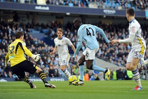 Manchester City's Yaya Toure, centre, slips past Leeds United goal keeper Jamie Ashdown, left, to score the first goal of the game for his side during their English FA Cup fifth round soccer match against Leeds United at the Etihad Stadium in Manchester, England, Sunday Feb. 17, 2013. (AP Photo/Clint Hughes)