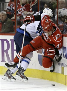 Winnipeg Jets' Chris Thorburn (22) checks Carolina Hurricanes' Michal Jordan (47), of the Czech Republic, during the first period of an NHL hockey game in Raleigh, N.C., Thursday, Feb. 21, 2013. (AP Photo/Gerry Broome)