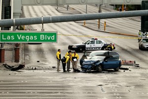 Law enforcement personal investigate the scene of a mulit-vehicle accident on Las Vegas Blvd and Flamingo Road Thursday, Feb. 21, 2013. Authorities say a Range Rover opened fire on a Maserati at a stoplight, sending it crashing into a taxi that went up in flames, leaving three people dead and at least six injured. Police were checking with nearby businesses to see whether a previous altercation prompted the car-to-car attack (AP Photo/Las Vegas Review-Journal, Jeff Scheid) LOCAL TV OUT; LOCAL INTERNET OUT; LAS VEGAS SUN OUT