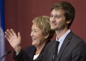 Leo Bureau-Blouin waves to people as he is sworn in as the youngest ever Quebec legislature member during a ceremony where the 54 elected members of the Parti Quebecois are sworn in Monday, September 17, 2012 at the legislature in Quebec City. Premier designate Pauline Marois, behind, looks on.A former leader within Quebec's student movement is taking flak from some of his old allies now that he's an elected politician and tuition fees are going up. THE CANADIAN PRESS/Jacques Boissinot