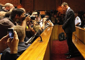 FILE - In this photo taken Friday, Feb. 22, 2013 Olympic athlete Oscar Pistorius stands in the dock during his bail hearing at the magistrate court in Pretoria, South Africa. Even if Pistorius is acquitted of murder, firearms and legal experts in South Africa believe that, by his own account, the star violated basic gun-handling regulations by shooting into a closed door without knowing who was behind it, exposing himself to the lesser but still serious charge of culpable homicide. (AP Photo/Themba Hadebe-File)