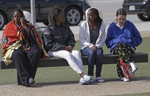 University of Central Florida students, from left, Antoinette Bennett, Stephanie Graham, Nathalie Fils-Aime and Stephanie Hintz, wait outside the college sports arena after they were evacuated from their nearby dorm when explosive devices were found, Monday, March 18, 2013, in Orlando, Fla. University police investigating the apparent suicide of a student at the Tower 1 dorm discovered the explosives in his room. (AP Photo/John Raoux)