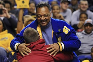 The Rev. Jesse Jackson embraces an unidentified man before the start of a second-round NCAA college basketball tournament game between Louisville and North Carolina A&T, Thursday, March 21, 2013, in Lexington, Ky. (AP Photo/James Crisp)