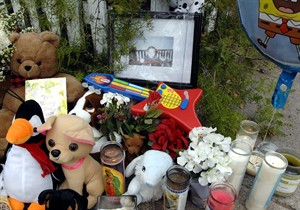 A photo, toys and candles are placed at a makeshift memorial for slain 13-month-old Antonio Santiago in Brunswick, Ga., Saturday, March 23, 2013. Antonio was shot dead in his stroller on Thursday. (AP Photo/Florida Times-Union, Terry Dickson)