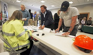 In this April 3, 2013 photo, people fill out applications at the Green Mountain Flagging table at the 4th Annual Central Vermont Job Fair in Montpelier, Vt. THE CANADIAN PRESS/AP, Toby Talbot