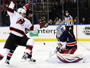 New York Rangers goalie Henrik Lundqvist, right, blocks a shot while New Jersey Devils' Dainius Zubrus, left, and Rangers' Anton Stralman jockey for position during the first period of an NHL hockey game, Sunday, April 21, 2013, in New York. (AP Photo/Seth Wenig)