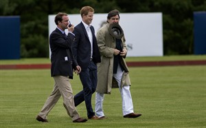 CORRECTS DATE MAY 15, 2013 Britain's Prince Harry walks across the polo field before the Sentebale Royal Salute Polo Cup charity match in Greenwich, Conn., Wednesday, May 15, 2013. Right is Peter Brant, founder of the Greenwich Polo Club. (AP Photo/Craig Ruttle)