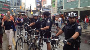 Toronto police officers line up along the Sammy Yatim march route on Monday, July 29, 2013.