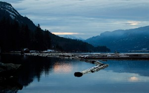 A worker uses a small boat to move logs on the Douglas Channel at dusk in Kitimat, B.C., in this Jan. 11, 2012 photo. THE CANADIAN PRESS/Darryl Dyck