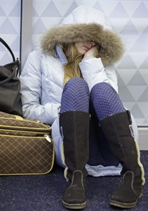 Anna Maksimkina of Yekaterinburg, Russia, sleeps on the floor at Kennedy International Airport after a Delta flight from Toronto to New York skidded off the runway into a snow bank, temporarily halting all flights, Sunday, Jan. 5, 2014, in New York. Authorities have said to to expect delays and flight cancellations because of the cold temperatures. (AP Photo/Kathy Willens)