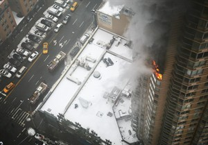 Flames and smoke emerge from the 20th floor of the Strand apartment building near Times Square, Sunday, Jan. 5, 2014 in New York. Authorities say two people have been critically injured in the three-alarm high-rise fire. (AP Photo/Katherine Bourbeau)