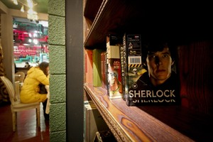 "In this photo taken on Friday, Jan. 17, 2014, a girl has a drink near books shelf displaying Sherlock Holmes books at a ""Sherlock""-themed cafe in Shanghai, China. ""Sherlock'' has become a global phenomenon, but nowhere more than in China, where fans' devotion is so intense that the BBC says this was the first country outside Britain where the new season was shown. (AP Photo)"