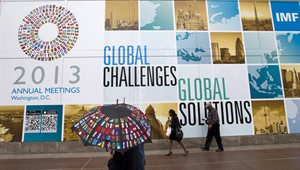 People walk in the rain outside International Monetary Fund (IMF) building in Washington, on Oct. 10, 2013. THE CANADIAN PRESS/AP, Jose Luis Magana