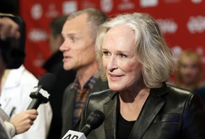 """Cast member Glenn Close speaks with reporters as fellow cast member Flea, rear, of the Red Hot Chili Peppers, is also interviewed at the premiere of the film """"Low Down"""" during the 2014 Sundance Film Festival, on Sunday, Jan. 19, 2014, in Park City, Utah. (Photo by Danny Moloshok/Invision/AP)"""