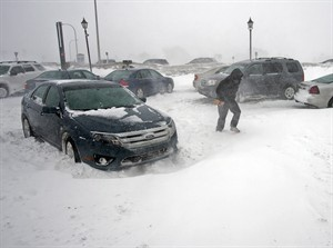 A stranded traveller crosses a parking lot at a service station in Borden-Carleton, Prince Edward Island on Sunday, Feb. 16, 2014. A major winter storm has battered the Maritimes with high winds, blowing snow and storm surges along the coast. THE CANADIAN PRESS/Andrew Vaughan