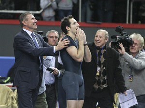 """France's Renaud Lavillenie, center, celebrates after setting a new world indoor record of 6.16 meters while legendary Sergey Bubka, left, congratulates the winner at the """"Pole Vault Stars"""" event at Donetsk in eastern Ukraine, Saturday, Feb. 15, 2014. Lavillenie broke Sergei Bubka's 21-year-old indoor pole vault world record. (AP Photo)"""