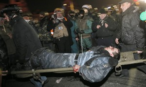 Anti-government protesters carry a wounded policemen during clashes with riot police in Kiev's Independence Square, the epicenter of the country's current unrest, Kiev, Ukraine, Wednesday, Feb. 19, 2014. Thousands of angry anti-government protesters clashed with police in a new eruption of violence following new maneuvering by Russia and the European Union to gain influence over this former Soviet republic. (AP Photo/Efrem Lukatsky)
