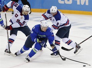 Slovenia forward Jan Urbas (26) take control of the puck from USA forward Patrick Kane (88) and USA forward Zach Parise (9) during the 2014 Winter Olympics men's ice hockey game at Shayba Arena Sunday, Feb. 16, 2014, in Sochi, Russia. (AP Photo/Petr David Josek)