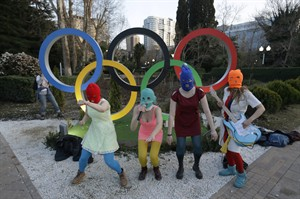 Members of the punk group Pussy Riot, including Nadezhda Tolokonnikova in the aqua balaclava, center, and Maria Alekhina in the red balaclava, left, perform next to the Olympic rings in Sochi, Russia, on Wednesday, Feb. 19, 2014. Cossack militia attacked the punk group with horsewhips earlier in the day as the artists - who have feuded with Vladmir Putin's government for years - tried to perform under a sign advertising the Sochi Olympics. (AP Photo/David Goldman)