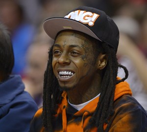 """FILE - In this Wednesday, Feb. 28, 2014 file photo, singer Lil Wayne watches the Los Angeles Clippers play the Houston Rockets during the first half of an NBA basketball game, in Los Angeles. Wayne reiterated his plans to make """"Tha Carter V"""" his last solo album and says the first single from the still-in-progress album will be out in the next week during an appearance at South By Southwest. The New Orleans rapper made the comments during a wide-ranging CRWN interview with Elliott Wilson on Friday, March 14, 2014, during the annual music conference and festival. (AP Photo/Mark J. Terrill, file)"""