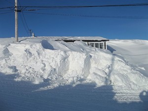 Janice Gould and Rick Cooper's house in Port au Choix, N.L., is almost completely buried under a thick blanket of snow on Wednesday, March 19, 2014. THE CANADIAN PRESS/ho-Janice Gould