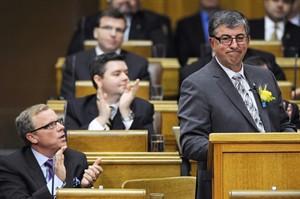 Saskatchewan Premier Brad Wall (left) applauds as Finance Minister Ken Krawetz delivers the provincial budget at the Legislative Assembly of Saskatchewan in Regina on Wednesday, Mar. 19, 2014. THE CANADIAN PRESS/Michael Bell