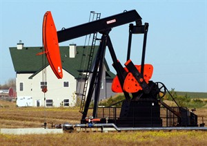 A pump jack dwarfs a house northwest of Calgary, in a Sept. 28, 2004 photo. THE CANADIAN PRESS/Jeff McIntosh