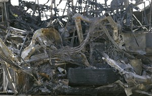 The burned interior of a tour bus that was struck by a FedEx truck on Interstate 5 Thursday is shown at a CalTrans maintenance station in Willows, Calif., Friday, April 11, 2014. At least ten people were killed and dozens injured in the fiery crash between the truck and a bus carrying high school students on a visit to a Northern California college. (AP Photo/Jeff Chiu)