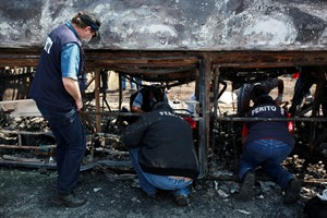 CORRECTS SPELLING OF PHOTOGRAPHER'S FIRST NAME - Forensic experts inspect a passenger bus that slammed into a broken-down truck and burst into flames near the town of Ciudad Isla in the Gulf state of Veracruz, Mexico, Sunday, April 13, 2014. Dozens of people traveling on the bus to Mexico City burned to death inside the bus. (AP Photo/Felix Marquez)