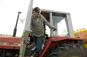 """FILE - In this Oct. 25, 2009, file photo Uruguay's President Jose Mujica stands in a tractor on his flower farm on the outskirts of Montevideo, Uruguay. Mujica has declared $322,883 in wealth in 2014. Uruguay's president has been labeled """"the poorest president in the world,"""" but his sworn declaration in 2014 shows a 74 percent increase since 2012. He says that's because didn't put his money, about $104,000, in bank accounts until recently. (AP Photo/Matilde Campodonico, File)"""