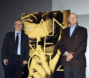 Cannes Film Festival general delegate Thierry Fremaux, left, and Festival President Gilles Jacob, right, pose next to the poster of the Festival, at the end of a press conference to announce this years line up in Paris, Thursday April 17, 204. A Tommy Lee Jones western and a David Cronenberg exposé on Hollywood are among the 18 films vying for the top prize at the Cannes Film Festival. The festival organizers also said Thursday that two women directors and famed New Wave filmmaker Jean-Luc Godard will be in competition at the festival that runs May 14-25.(AP Photo/Remy de la Mauviniere)
