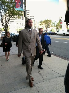 Singer Chris Brown's bodyguard, Christopher Hollosy leaves a District of Columbia courthouse in Washington, Thursday, April 17, after the first day of his trial on an assault charge. Both the singer and his bodyguard were arrested in October after a man accused them of punching him outside a Washington hotel. (AP Photo/Jessica Gresko)