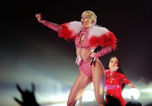 FILE - In this Saturday, April 5, 2014 file photo, singer Miley Cyrus performs at the Barclays Center in New York. Cyrus is postponing her U.S. tour while she recovers from an allergic reaction to antibiotics, but will resume her performances in August 2014. Cyrus' representative tells The Associated Press on Friday, April 18, 2014, that the singer will resume the U.S. tour Aug. 1 in Uniondale, N.Y. (Photo by Evan Agostini/Invision/AP, file)