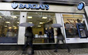 Pedestrians pass a branch of Barclays Bank in the rain in London, May 8, 2014. THE CANADIAN PRESS/AP, Kirsty Wigglesworth