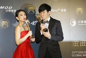 Malaysian singer Penny Tai, left, and Singapore singer JJ Lin kiss their awards for Best female Mandarin singer and Best male Mandarin singer, at the 25th Golden Melody Awards in Taipei, Taiwan, Saturday, June 28, 2014. The Golden Melody Awards are one of the Chinese-language pop music world's biggest annual events. (AP Photo/Wally Santana)