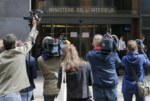 Members of the media stand in front of the entrance to the anti-corruption office of the French police, Tuesday, July 1, 2014 in Nanterre, near Paris. Former French President Nicolas Sarkozy has been detained and was reportedly being questioned by financial investigators Tuesday in a corruption probe that is rattling France's conservative political establishment. A judicial official said Sarkozy was in custody in the Paris suburb of Nanterre. (AP Photo/Jacques Brinon)