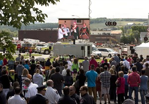 People watch the mass outside the church on a screen overlooking downtown Sunday, July 6, 2014 in Lac-Megantic, Que.THE CANADIAN PRESS/Ryan Remiorz