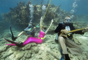 In this photo provided by the Florida Keys News Bureau, participants Nancy Barta, left, Samantha Langsdale center, and Fernando Barta pretend to play mock musical instruments and enjoy the Lower Keys Underwater Music Festival on Saturday, July 12, 2014, in the Florida Keys National Marine Sanctuary, at Looe Key Reef near Big Pine Key, Fla. Nearly 500 divers and snorkelers listened to a local radio station's four-hour broadcast piped beneath the sea via underwater speakers. (AP Photo/Florida Keys News Bureau, Bob Care)