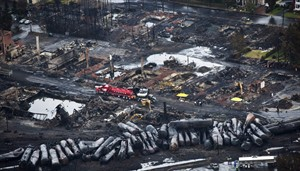 Workers comb through debris after a train derailed causing explosions of railway cars carrying crude oil in Lac-Megantic, Quebec, July 9, 2013. THE CANADIAN PRESS/Paul Chiasson