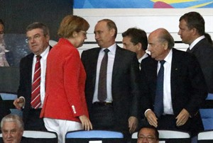 German Chancellor Angela Merkel, second left, walks past IOC president Thomas Bach, left, Russian President Vladimir Putin, third left, and FIFA President Sepp Blatter, right, during the World Cup final soccer match between Germany and Argentina at the Maracana Stadium in Rio de Janeiro, Brazil, Sunday, July 13, 2014. (AP Photo/Frank Augstein)
