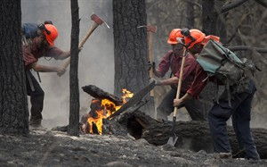 Firefighters tackle a flare up at the Smith Creek fire located on a hillside in West Kelowna, B.C., Saturday, July, 19, 2014. Cooler weather and rainfall in parts of British Columbia have helped to quell wildfires across the province, but some areas in the southern and central interior are still facing an extreme danger rating. THE CANADIAN PRESS/Jonathan Hayward