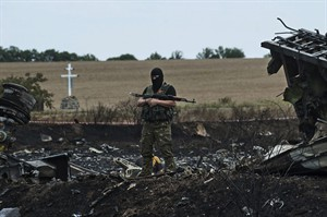 A pro-Russian fighter guards the crash site of Malaysia Airlines Flight 17 near the village of Hrabove, eastern Ukraine, Sunday, July 20, 2014. Rebels in eastern Ukraine took control Sunday of the bodies recovered from downed Malaysia Airlines Flight 17, and the U.S. and European leaders demanded that Russian President Vladimir Putin make sure rebels give international investigators full access to the crash site.(AP Photo/Evgeniy Maloletka)