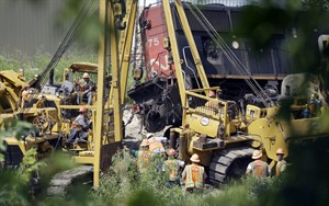 Workers clean up a train derailment Monday, July 21, 2014, in Slinger, Wis. A southbound Canadian National train struck several Wisconsin & Southern Railroad cars around 8:30 p.m. Sunday at a rail crossing in Slinger, Wic.,according to Patrick Waldron, a Canadian National spokesman. The derailment injured at least two people and spilled thousands of gallons of fuel that prompted the evacuation of dozens of homes, but evacuees were allowed to return around 1:30 a.m. Monday, Slinger Fire Chief Rick Hanke said. (AP Photo/Morry Gash)