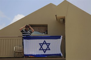 A man uses binoculars to look at the Gaza Strip from his balcony in the town of Sderot after a group of Hamas militants was detected infiltrating into Israel, Monday, Jul(y 21, 2014. The Israeli military said 10 infiltrators were killed after being detected and targeted by Israeli aircraft. Israel invaded Gaza late last week, preceded by a 10-day air campaign. (AP Photo/Tsafrir Abayov)