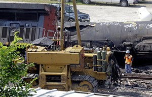 Workers clean up a train derailment Monday, July 21, 2014, in Slinger, Wis. A southbound Canadian National train struck several Wisconsin & Southern Railroad cars around 8:30 p.m. Sunday at a rail crossing in Slinger, Wis., according to Patrick Waldron, a Canadian National spokesman. The derailment injured at least two people and spilled thousands of gallons of fuel that prompted the evacuation of dozens of homes, but evacuees were allowed to return around 1:30 a.m. Monday, Slinger Fire Chief Rick Hanke said. (AP Photo/Morry Gash)